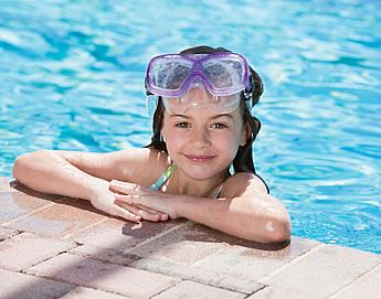 Young girl at the edge of the pool with goggles on her head