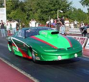 A green car on a drag racing strip.