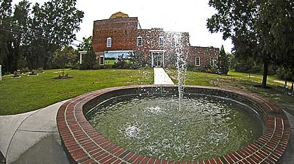 A brick fountain with a building in the background.